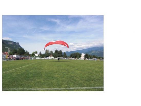 Atterrissage du parapente sur le stade de foot